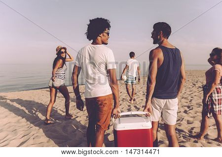 Ready to beach party. Group of cheerful young people walking by the beach to the sea while two men carrying plastic cooler