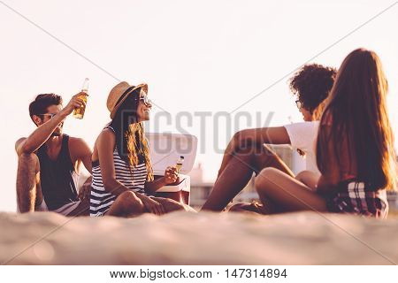Beach picnic with friends. Cheerful young people spending nice time together while sitting on the beach and drinking beer
