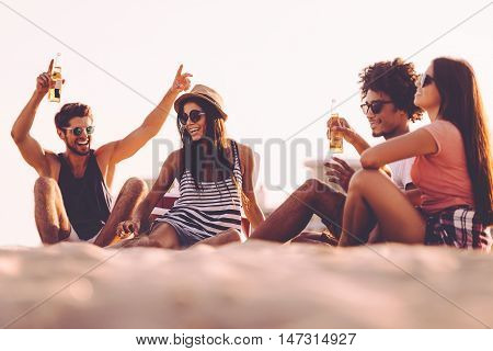 Spending carefree time with friends. Cheerful young people spending nice time together while sitting on the beach and drinking beer