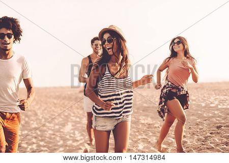 Young and carefree. Group of young cheerful people running along the beach and looking happy