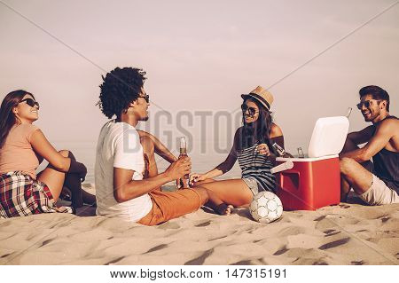 Beach time. Cheerful young people spending nice time together while sitting on the beach and drinking beer