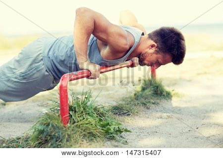fitness, sport, exercising, training and lifestyle concept - young man doing push ups on horizontal bar outdoors