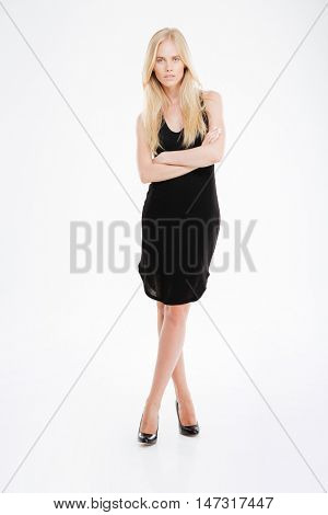 Full length portrait of a beautful woman in black dress standing with arms folded isolated on a white background
