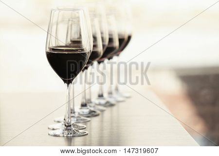 Glasses with red wine in a row on a table