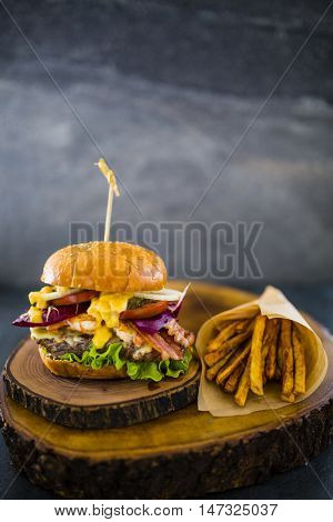 Tasty grilled beef and prawn burger with lettuce and mayonnaise in crispy shortbread with lettuce and mayonnaise served with french fries on small cutting board.