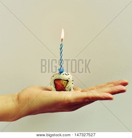 closeup of the hand of a young man holding a California roll topped with a lit cake candle, against an off-white background
