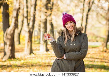 Portrait of young blonde Caucasian woman in olive green jacket and dark red knitted beanie hat, holding apple in park in autumn, smiling. Cheerful teenage girl outdoors in fall.