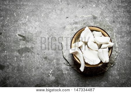 Coconut pulp in a bowl . On a stone background.