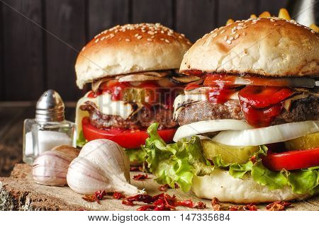 Two burgers with mushrooms tomatoes cucumbers salat cheese and onions on a wooden base with garlic close-up