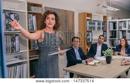 Portrait of female coach explaining project management studies to business team at table in the background