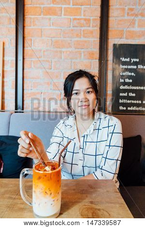 Cute Asian Girl Drinking Latte Art Coffee At Cafe