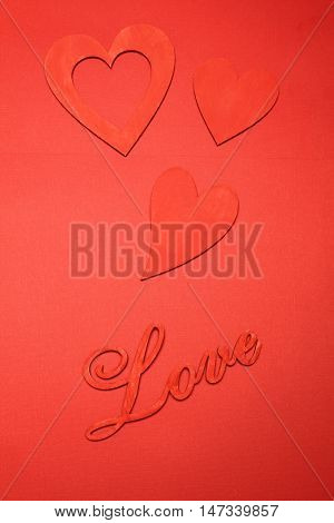 Love wooden letters on the background of the little red hearts