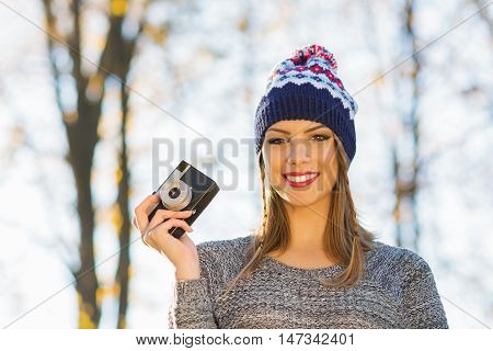 Young female photographer in autumn in park. Closeup of blonde teenage girl in beanie and sweater, holding analogue camera, outdoors on sunny fall day.