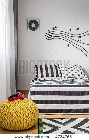Light bedroom with music wall decor pattern bedding and headphones lying on a pouf