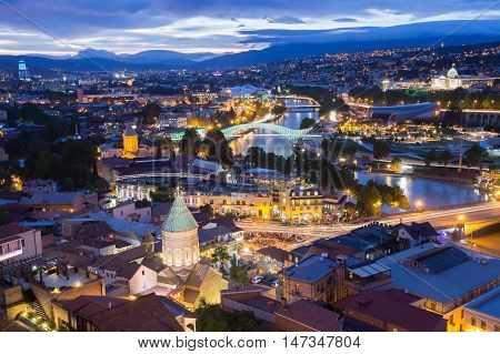 Scenic Top View Of Tbilisi, Georgia In Evening Lights Illumination. Metekhi Bridge, Surb Gevorg Church And All Famous Landmarks, Sightseeings Under Beautiful Blue Cloudy Sky. poster