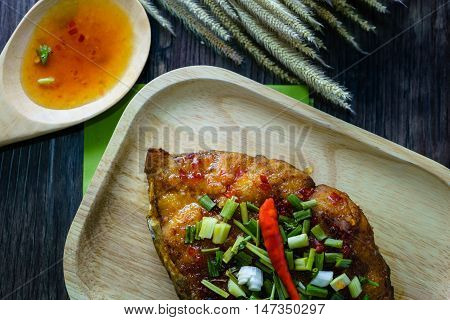 King Mackerel serve with sauce in Thai menu food Fresh fish fried in Asian food style on the wood table