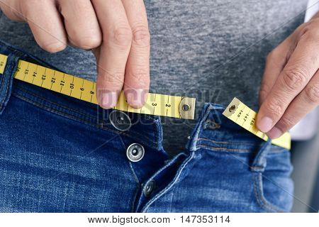 a young man with a measuring tape as a belt tries to fasten his trousers, because of the weight gain poster