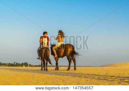JERICOACOARA, BRAZIL, DECEMBER - 2015 - Couple riding horse at the beach in Jericoacoara Brazil