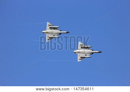 Two fighter jets flyby on a blue sky.