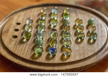 Marbles Solitaire Glass Spheres on wooden board groove around