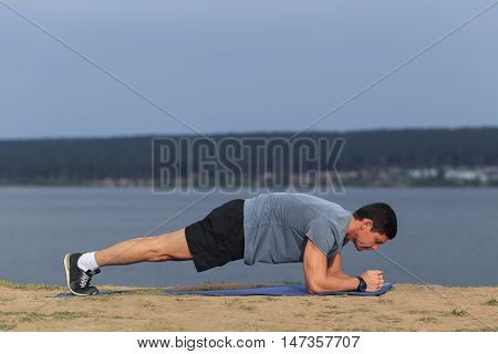 Crossfit training fitness man doing plank core exercise working out his midsection core muscles. Fit male fitness instructor planking exercising outside in summer