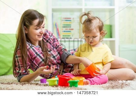 Kid with babysitter playing on floor in the room