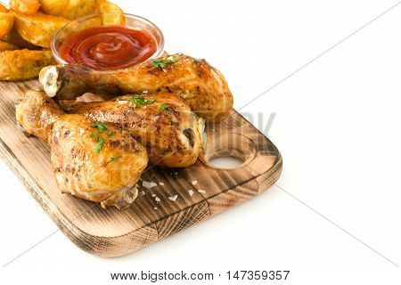 Roast chicken drumsticks and chips on cutting board isolated on white background