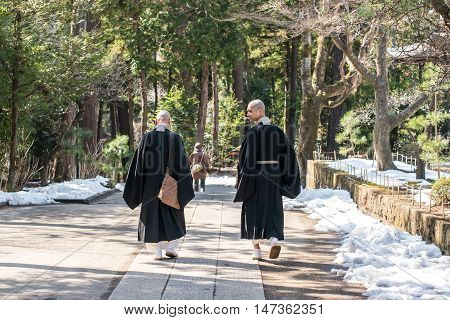 Kamakura, Japan - February 21 2014 - Two monks walking inside the Engaku Ji sacred complex Kamakura Japan