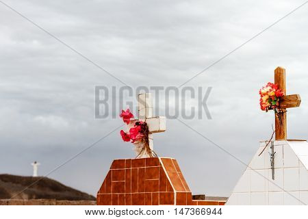 Two Crypts With The Statue Of Christ In The Background In A Small Cemetery In Catamarca, Argentina