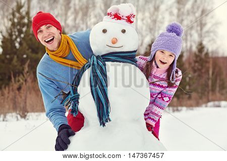 funny dad and daughter with a snowman. Family walking outdoors in winter