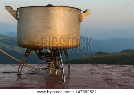 Old pan on a gas burner camp standing on a board on background of mountains