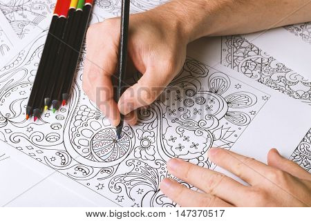 Man's hands and colored pencils placed above adult coloring book. In the process of painting.