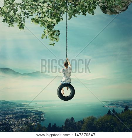 Young boy swinging on a tire over the foggy city with lake and forest background. Having fun and freedom concept