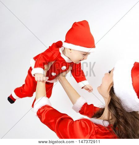 Mother and baby dressed in Christmas Santa costumes. Mother and baby playing together