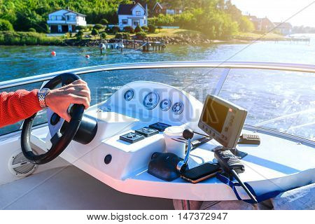 Hand of captain on steering wheel of motor boat on canal. Evening sunshine gives nice warm atmosphere to the scene poster