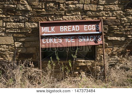 Old rusted antique vintage sign advertising milk bread eggs cokes ice and snacks for an abandoned store resting against a stone wall.