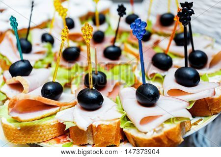 Catering service plate. Appetizing sandwiches on plastic sticks range. Sandwiches on a table the buffet. meat fish vegetable canapes on a festive wedding table outdoor