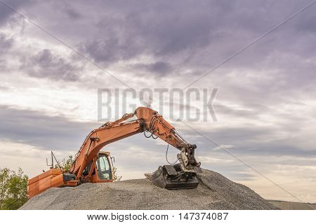 Hydraulic excavator climbed on a ballast pile - Heavy orange excavator with big bucket working on top of a ballast pile.