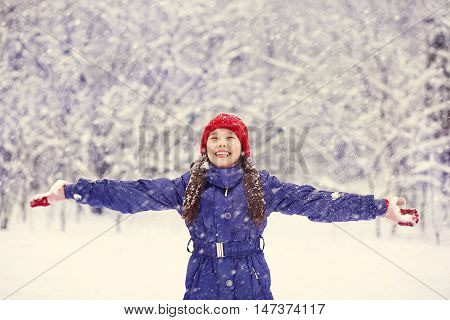 happy girl walking in the winter outdoors. teen playing with snow. child outdoor