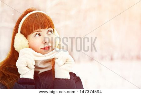 portrait of redhead woman on the winter walk in the park. people outdoors