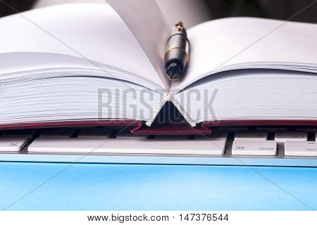 Close-up of open book computer and pen. Copy space for text.