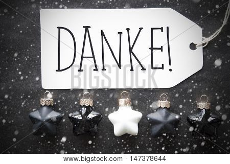 Label With German Text Danke Means Thank You. Black And White Christmas Tree Balls On Black Paper Background With Snowflakes. Christmas Decoration Or Texture. Flat Lay View