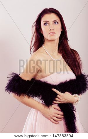 Beauty fashion and elegant people concept - young brunette slim woman in bright dress black boa feather bare shoulders