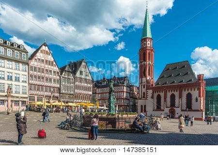 Frankfurt Germany - April 28 2016: Tourist at old traditional buildings in Frankfurt Germany in a summer day. Romerberg town square in Frankfurt Germany