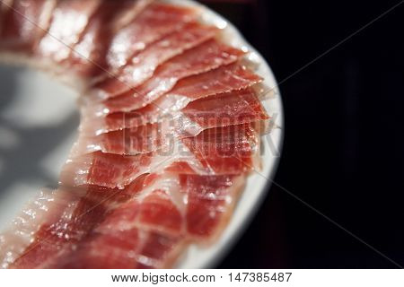 Half decorated arrangement of iberian cured ham on plate isolated over black background