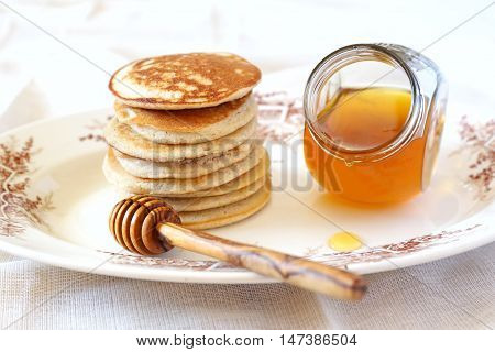 Thick Pancakes with honey on vintage plate