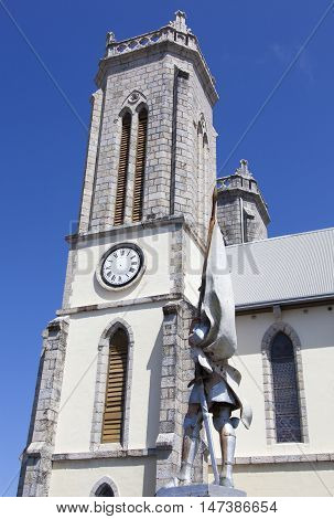 The tower of Saint Joseph's Cathedral with the statue of Joan of Arc next to (Noumea New Caledonia).