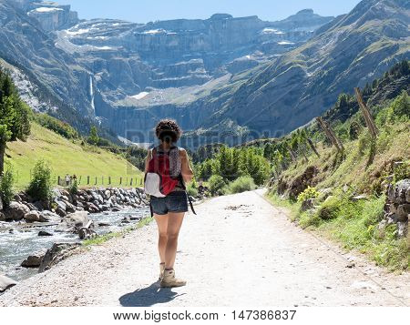 A woman hiker and cirque de Gavarnie in the French pyrenees mountains