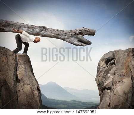 Man carries a trunk in a crevice between two mountains