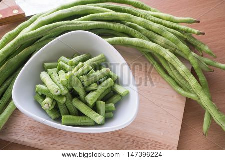 Sliced yard long bean vegetable on the white dish and wooden block Asian's homegrown vegetable View from top vegetable.